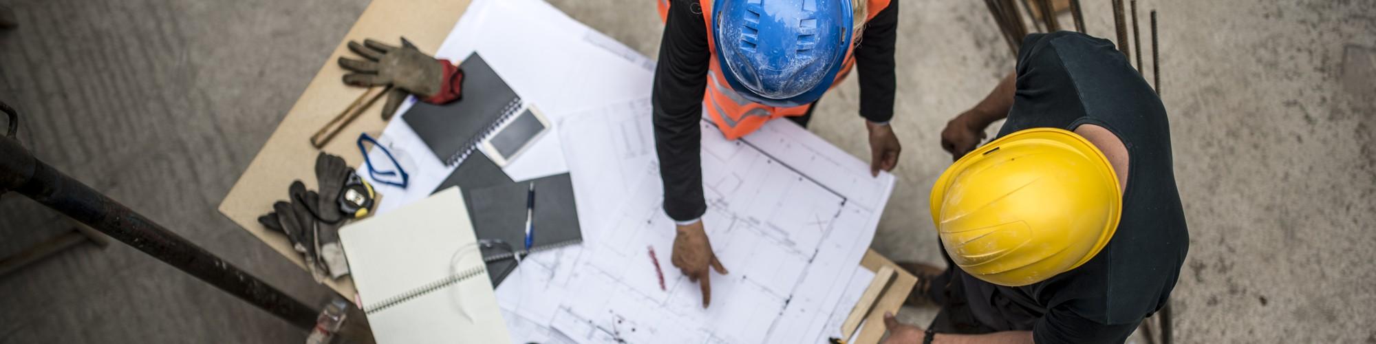 Bild: Baupläne auf Tisch von oben gesehen mit zwei Bauarbeitern, die diese betrachten