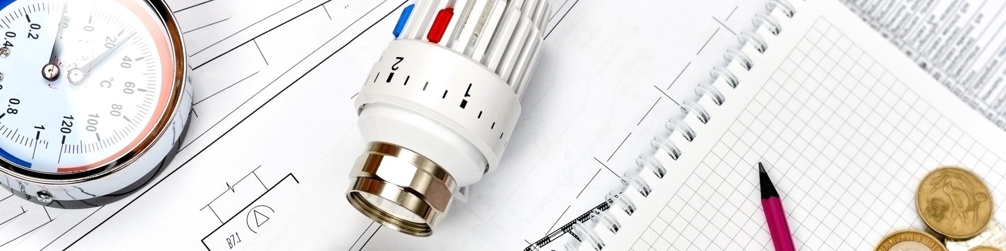 Foto Thermostat und Thermometer liegen auf Zeichnungen