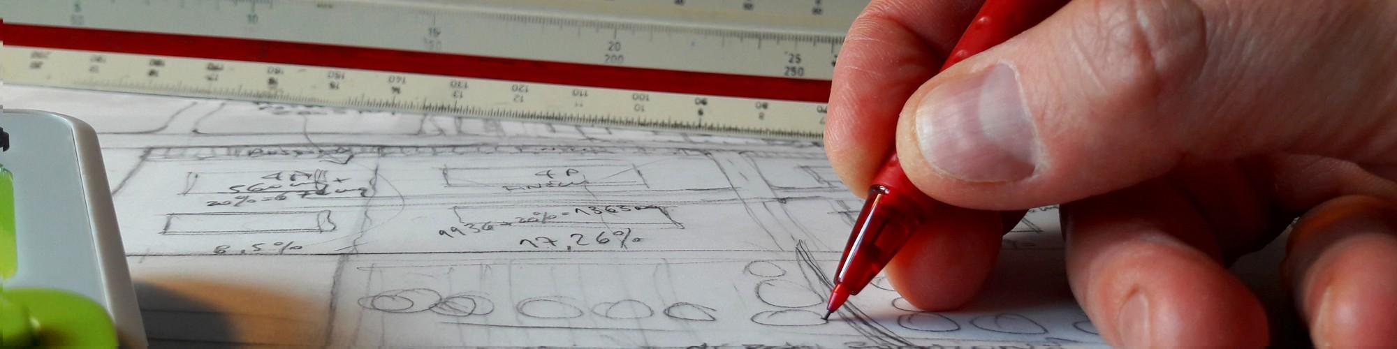 Bild: Hand mit Stift und Maßstabslinieal auf Bauzeichnung